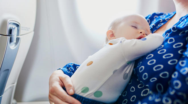 mom holding sleeping baby while on flight