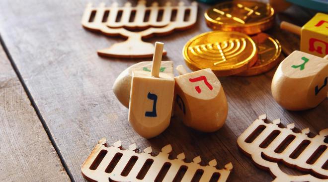 dreidels and menorahs representing hanukkah gift guide