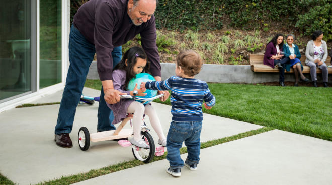 grandfather playing with his toddler age grandkids in the backyard