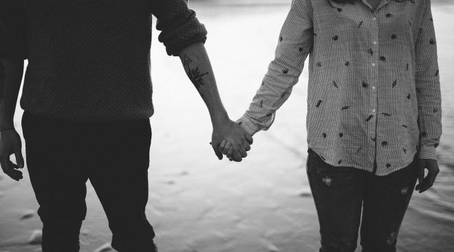 black and white image of serious couple holding hands near water