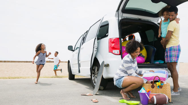 happy family unloading their car at the beach