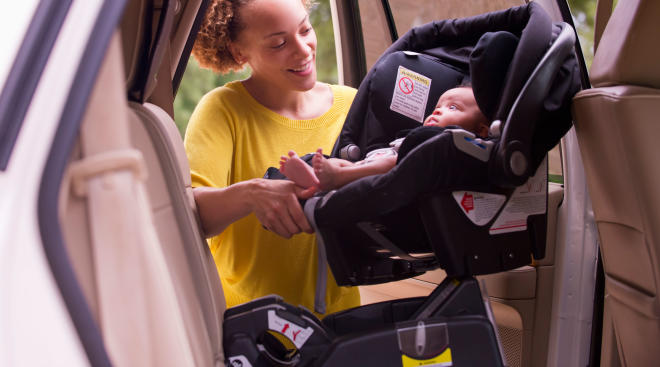 mom puts baby into securely installed car seat