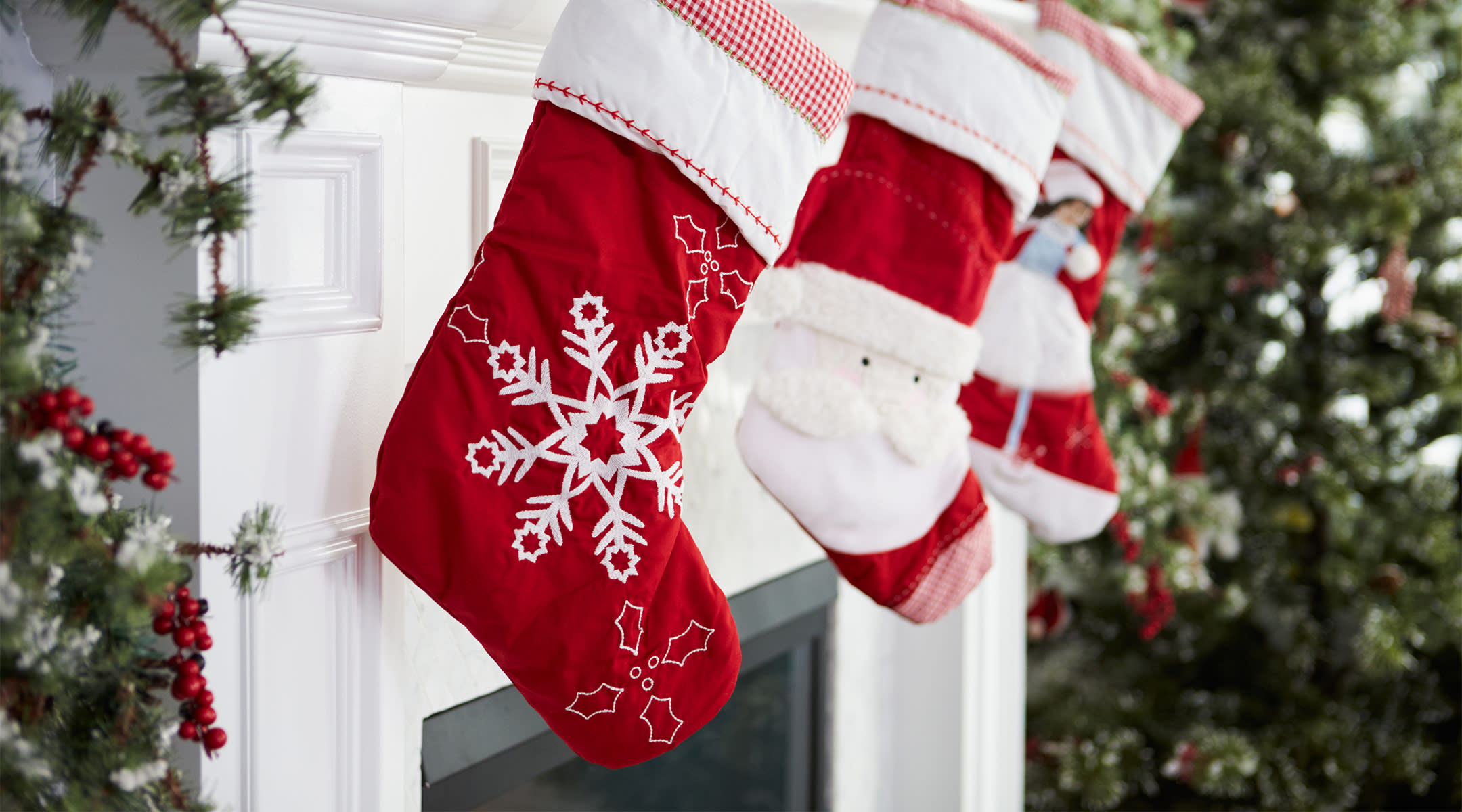 red christmas stockings hang over fireplace