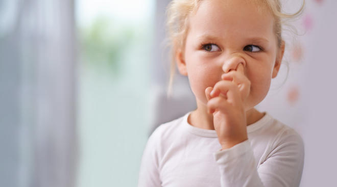 Young blonde girl picking her nose