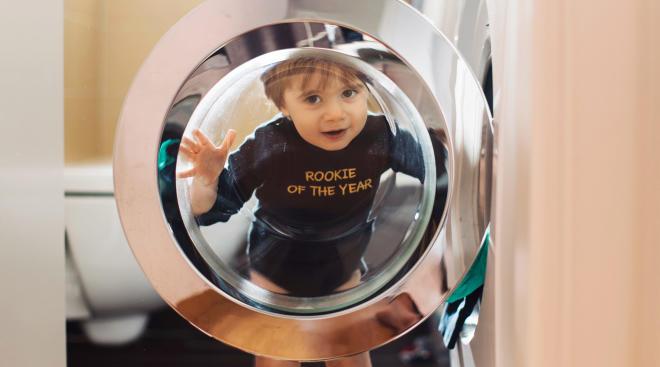 mischievous toddler standing by open dryer