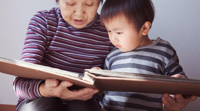 grandma and grandson look through keepsake photo album