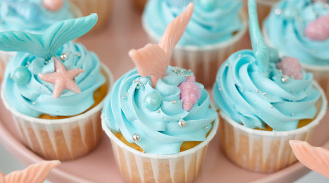 cupcakes with blue frosting and mermaid tail decoration