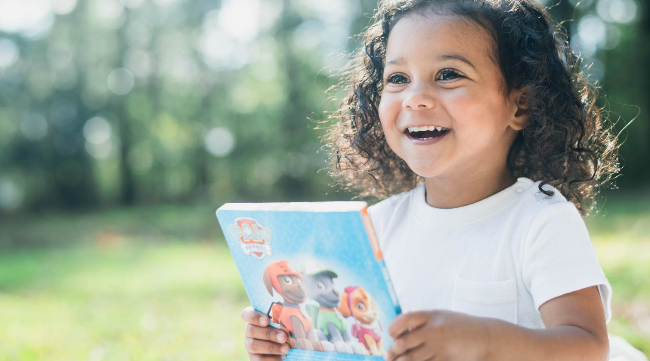 Happy toddler outside holding book.