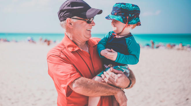 grandpa and toddler wearing hat for sun protection, on the beach