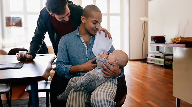 parents at home holding happy baby