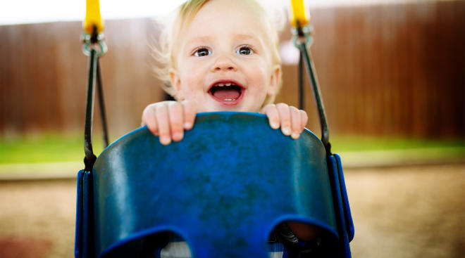 happy baby on playground swing outside