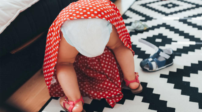 toddler girl wearing diaper bent over