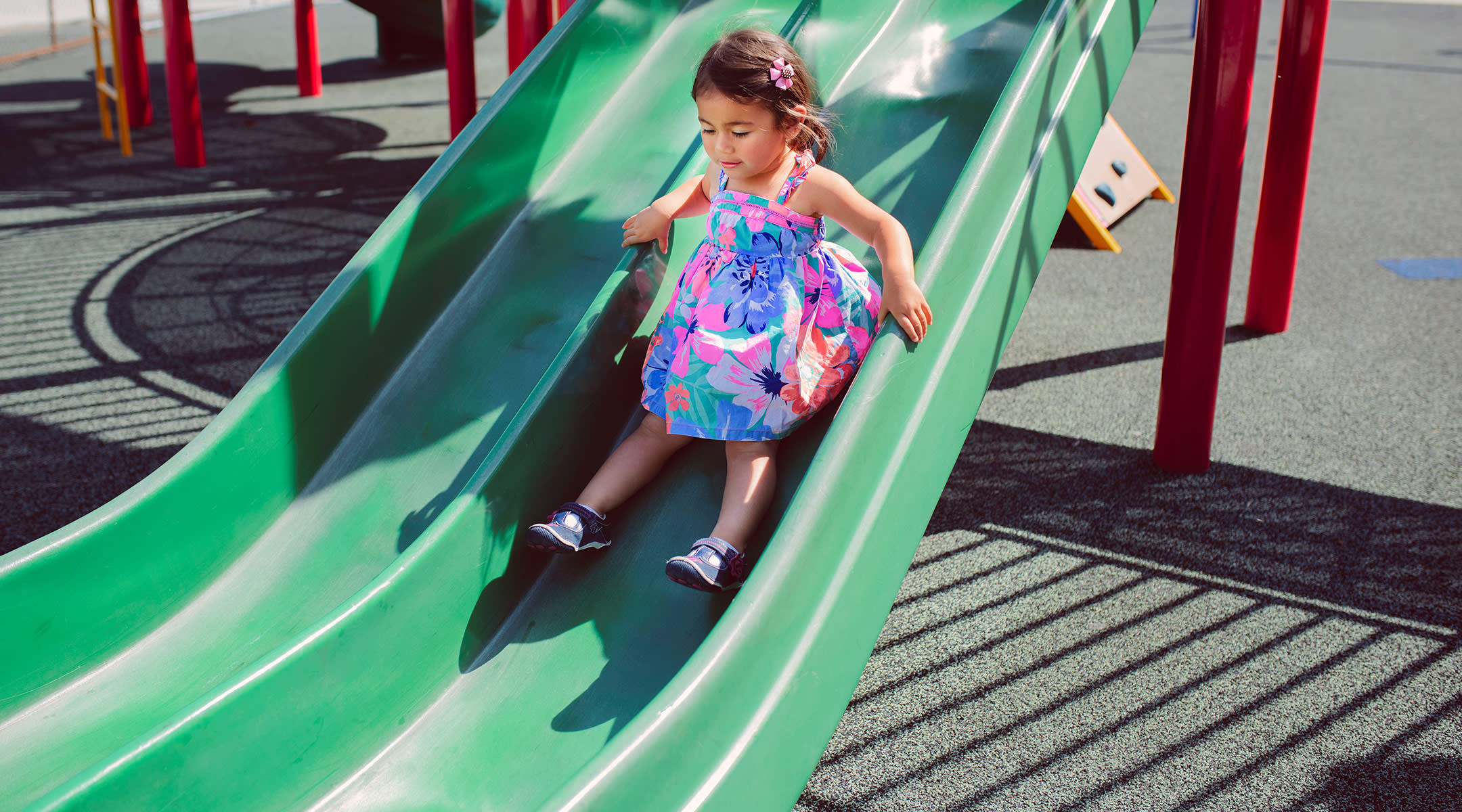 toddler girl going down playground slide