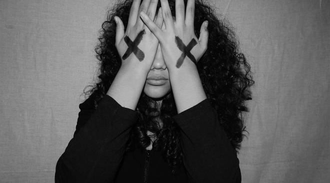upset woman covering her face with her hands. Her hands have x's drawn on them.