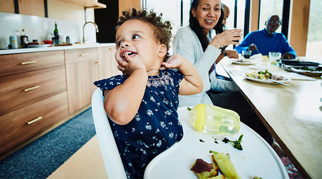 toddler eating in her high chair with family around