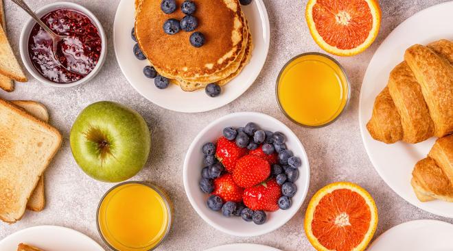 breakfast food spread including croissants, fruit, toast, and orange juice