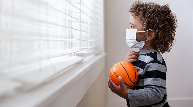 worried child looking out the window and holding a basketball