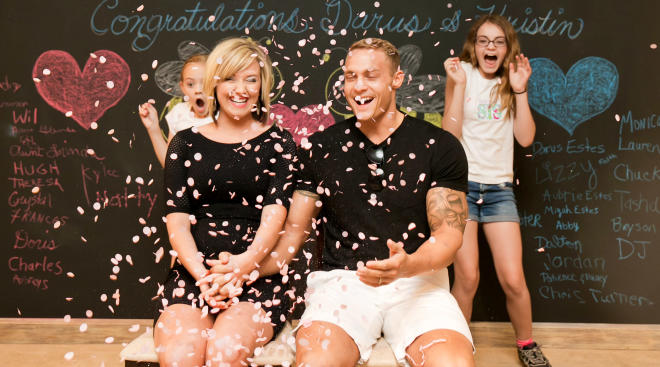family hosting gender reveal party surrounded by pink confetti signifying baby girl