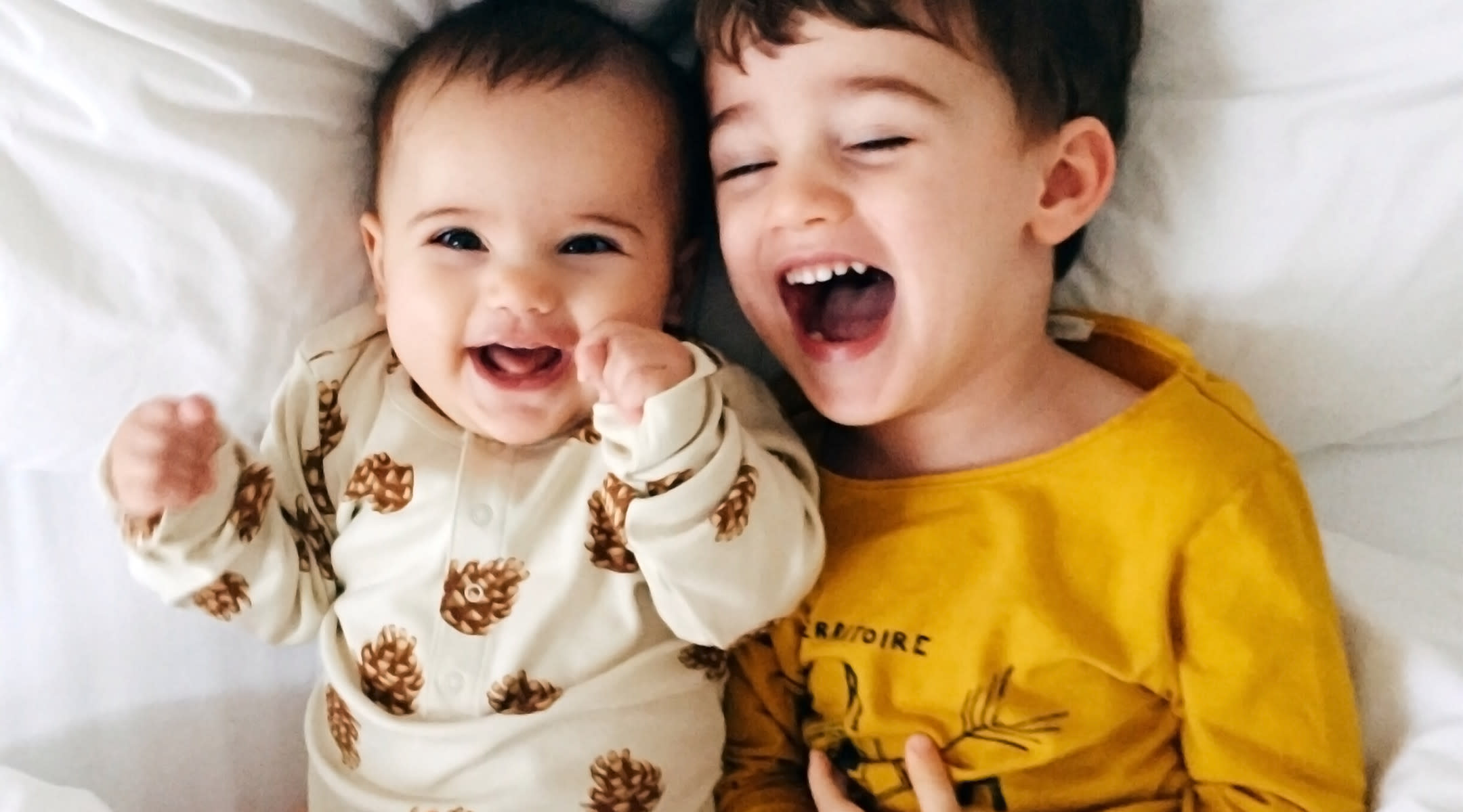 baby and big brother lay in bed laughing
