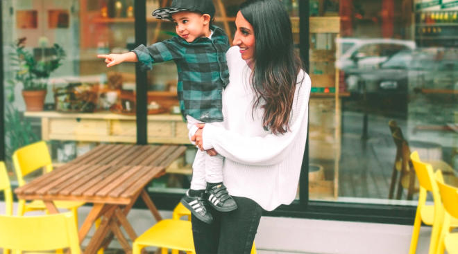 mom holding toddler son and having conversation