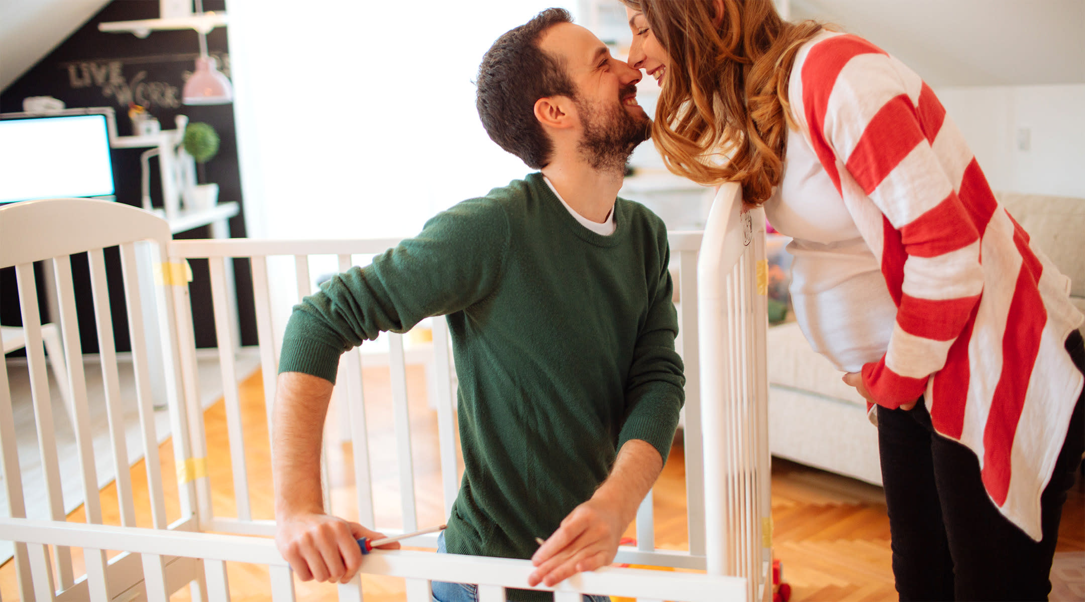 Pregnant woman affectionately rubbing noses with her partner who is building a baby crib.