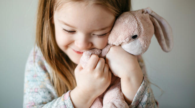 smiling toddler holds bunny doll