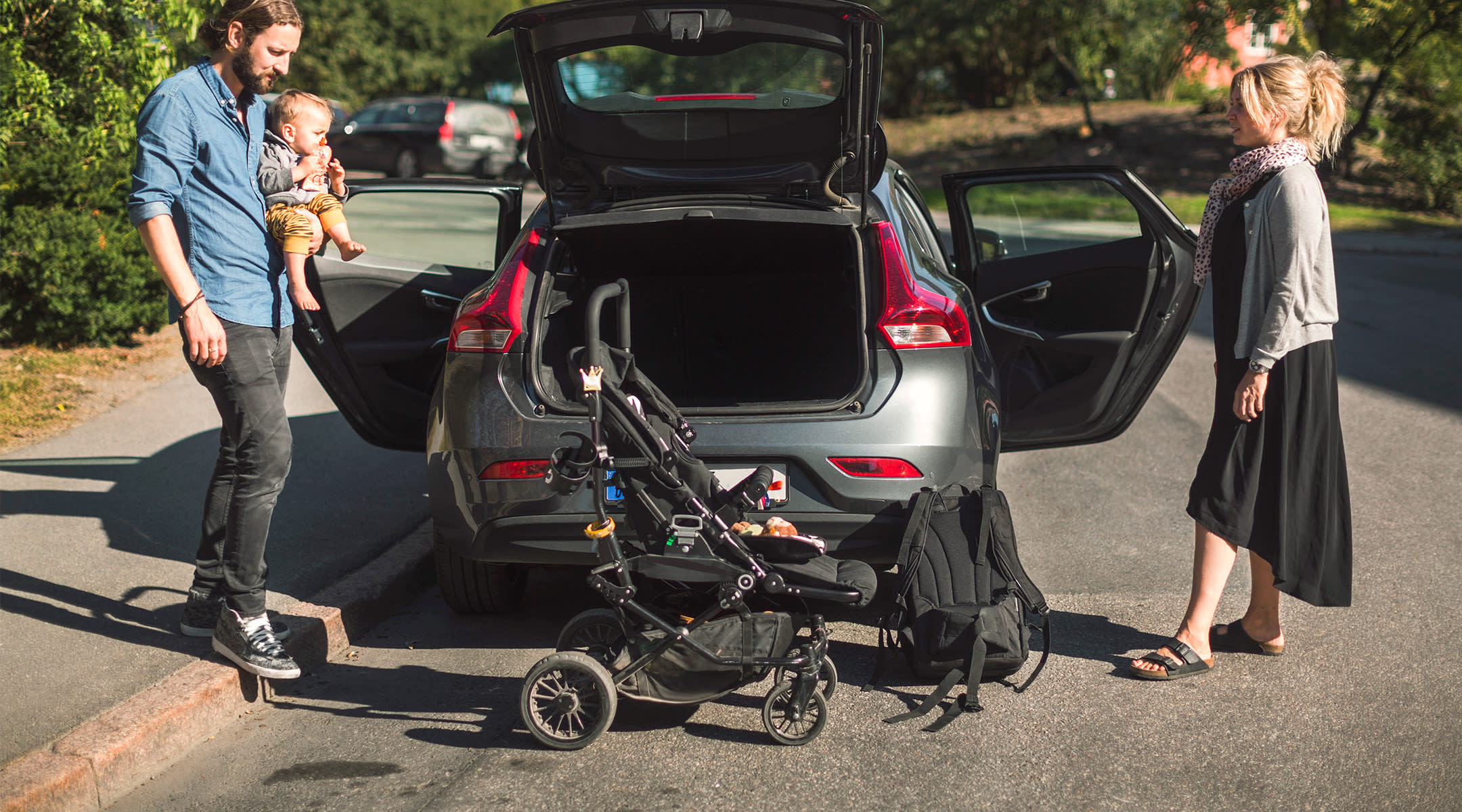 parents getting ready to put baby and stroller in their car