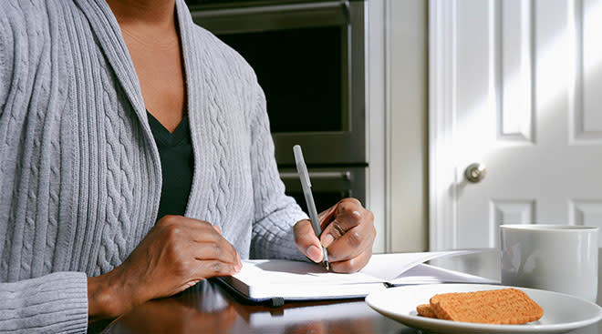 mid section of woman's hands sitting at table and writing in a journal
