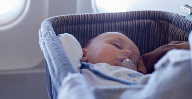 Baby sleeping in a cot on an airplane