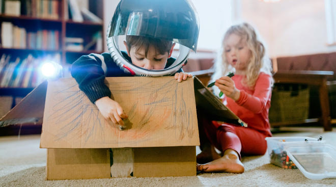 two children playing make space ship believe with a cardboard box