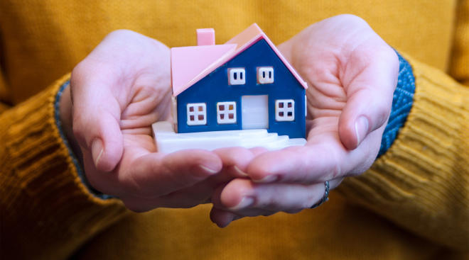 hands holding miniature house