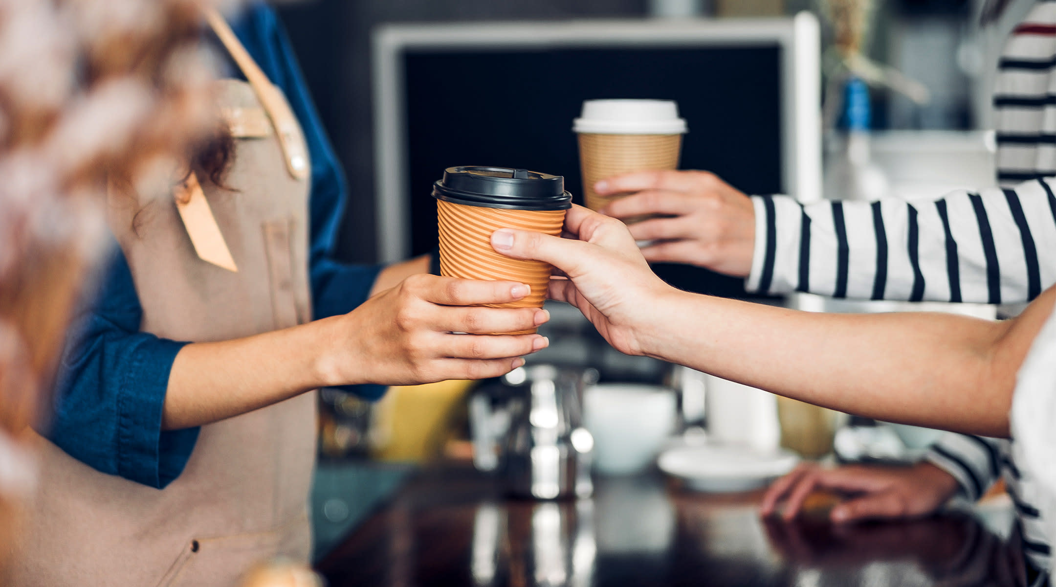 barista handing coffee to customers at coffee shop