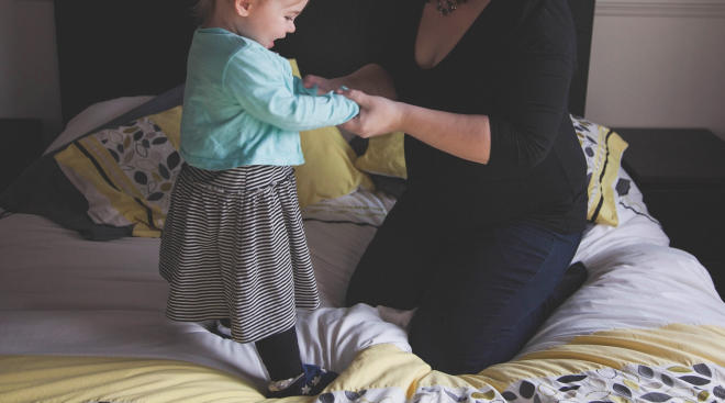 toddler girl on bed embracing mom