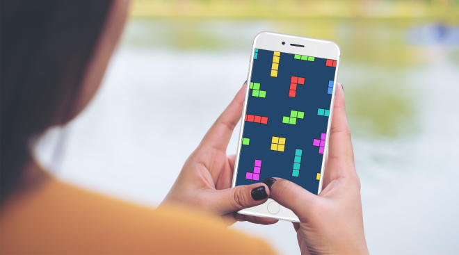 woman finding stress relief by playing tetris on her phone