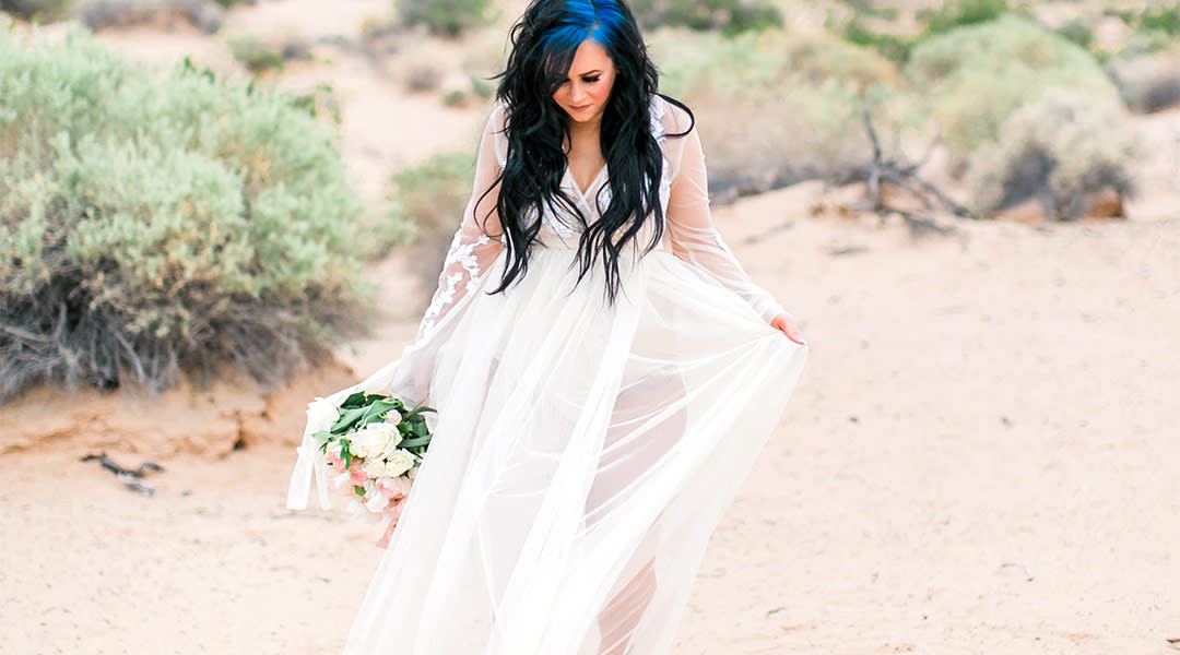 pregnant woman wearing white flowy maternity shoot dress on the beach