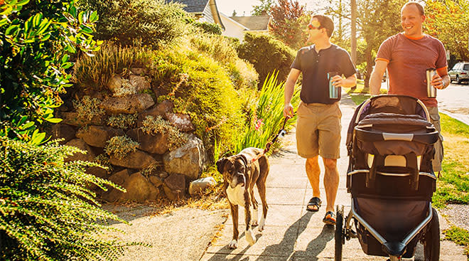 dads walking their baby in a stroller in residential neighborhood