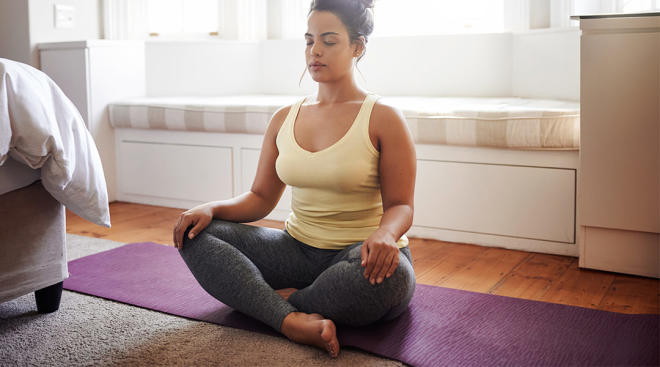 calm woman sitting in her bedroom and doing a breathing exercise on yoga mat