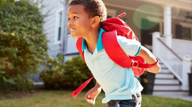 happy little boy walking to school
