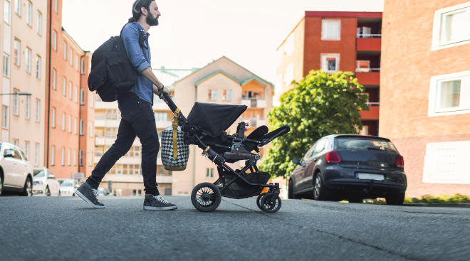 dad pushing baby stroller and carrying diaper bag