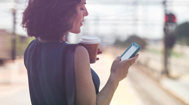 Woman with bag on shoulder waiting and looking at phone.