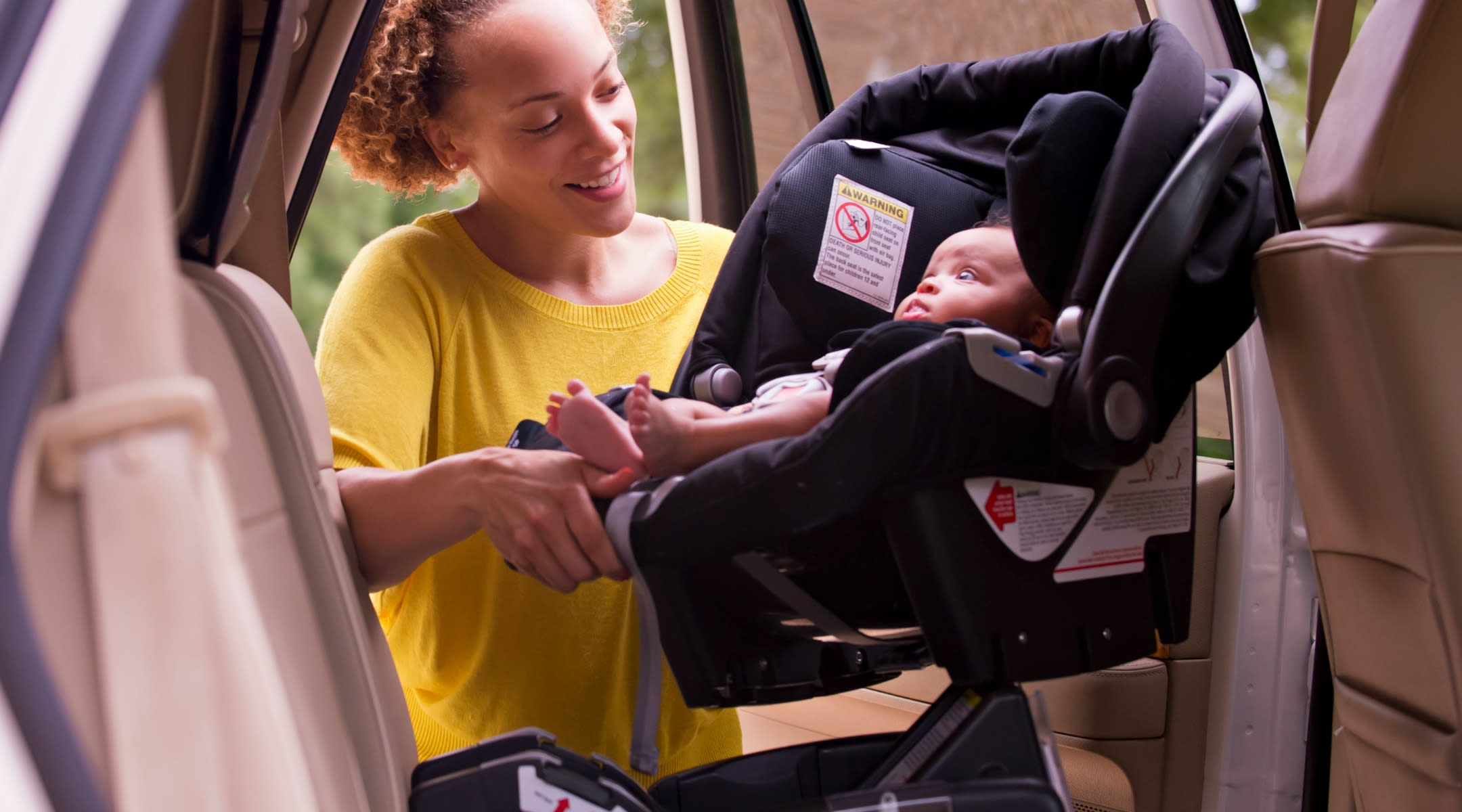 mom putting baby in rear-facing car seat