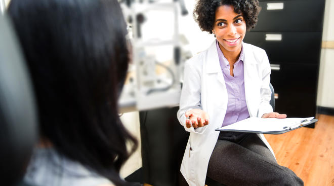 doctor speaking with female patient medical office