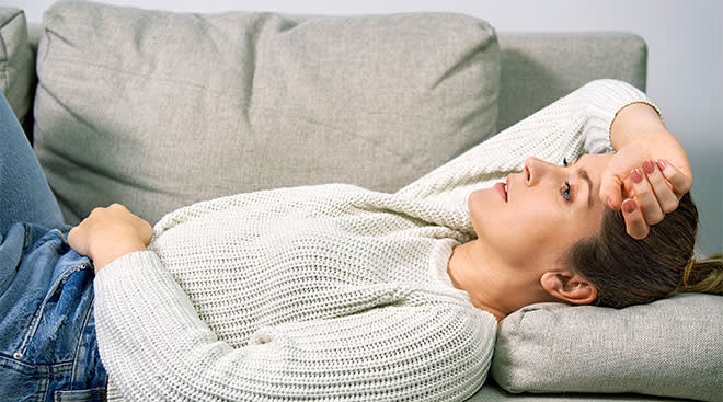 Woman laying on couch in pain, experiencing morning sickness.
