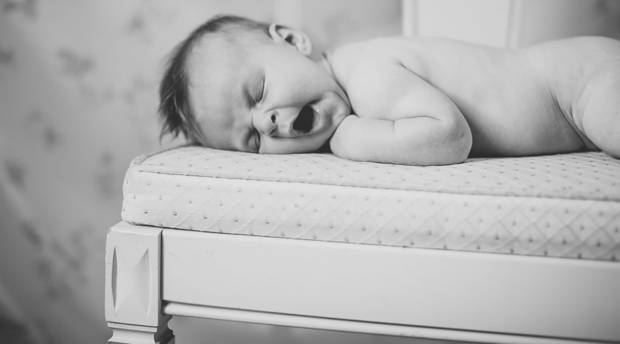 A black-and-white image of a yawning baby