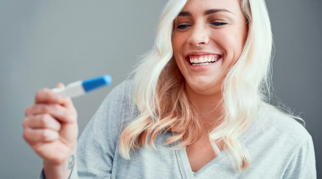 happy woman holding positive pregnancy test