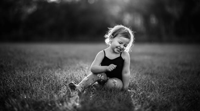 toddler girl sitting and candidly laughing outdoors