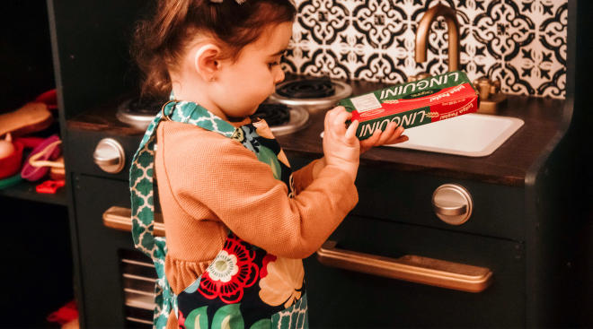 toddler practicing autonomy in play kitchen
