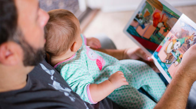 dad holding baby on his lap and reading to her