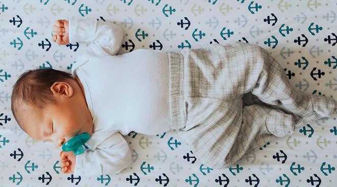 Newborn baby sleeping on its back on anchor pattern crib sheets,