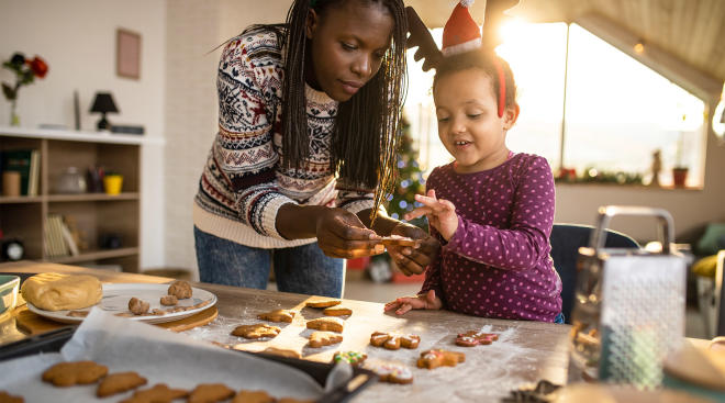 mom helps her daughter with christmas crafts